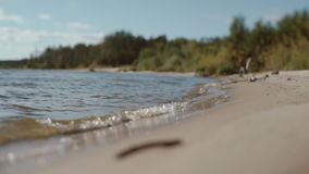 The sandy bank of the river with the oncoming wave stock footage
