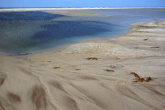 Sandy Bay Beach with beautiful color of the water and dunes in the background Stock Photography