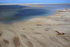 Sandy Bay Beach mit schöner Farbe des Wassers und der Dünen im Hintergrund Stockfotografie