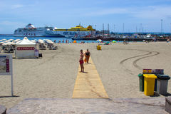 The sandy bay at and ferry terminal at Los Cristianos in Tenerife with island ferries in port and holiday makers walking the beach Stock Photo