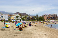 The sandy bay at Los Cristianos in Tenerife with holiday makers sun bathing and hotels and mountains in the background. The sandy bay at Los Cristianos in Royalty Free Stock Image