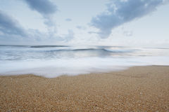Sandy Beach. Clean sandy beach with blue sky and clouds with motion blurred waves royalty free stock photography