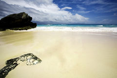Sandy beach. A view of a wide sandy beach with white surf, clouds and rocks Stock Images