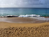 Sandy Beach. Waves crashing on a sandy beach before a storm comes in Stock Photos