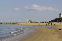 Sandy beach in Arcachon, south-west of France. Sandy beach in the city of Arcachon in the south-west of France with people walking and kids playing Stock Photo
