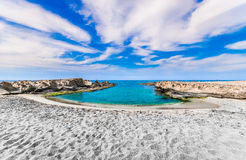Sandy beach around a small gulf. White sandy beach under cloudy blue sky in Crete stock image