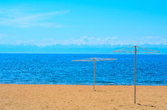 Sandy beach and blue lake. Sandy beach with two umbrellas and blue water lake Royalty Free Stock Photo