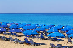 Sandy beach with blue parasols and sunbeds Stock Photo