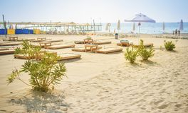 Sandy beach on blue sea background. Umbrellas and deck chairs on shore of sea. Summer day on beach rest. Vacation concept. View on sea beach in sunny clear day Royalty Free Stock Photos