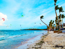 Sandy beach, blue sea, waves and palm trees bendable by flows strong sea wind. stock image