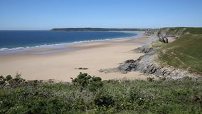 Sandy beach and blue sea and waves in summer at The Gower peninsula South Wales UK stock footage
