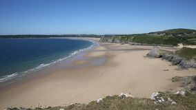 Sandy beach blue sea and waves in summer at The Gower peninsula South Wales UK by Three Cliffs Bay stock video