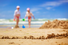 Sandy beach with blur sea on background. A fence of sand on the background of children playing in the sea. blurred background Stock Photography
