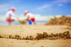 Sandy beach with blur sea on background. A fence of sand on the background of children playing in the sea. blurred background Stock Photo