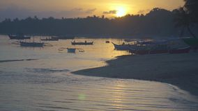 Sandy beach with boats at sunset stock video