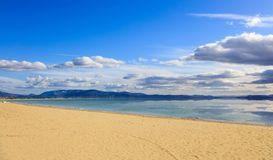 Sandy beach, calm sea, blue sky with few white clouds background. Summer destination. Reflection on sea of clouds and mountains. Sandy beach, calm sea, blue sky Stock Photo