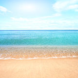 Sandy beach with calm water against blue skies. Royalty Free Stock Image
