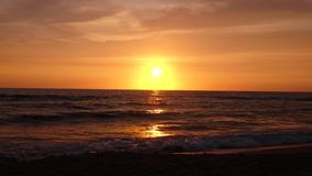 Sandy beach with choppy waves of the sea at sunset. Sandy beach with choppy foamy waves of the sea at sunset the background of the cloudy sky stock video footage