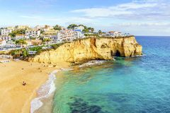 Sandy beach between cliffs in front of white architecture of Car. Sandy beach between cliffs in front of charming white architecture of Carvoeiro and turquoise Royalty Free Stock Images
