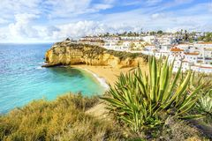 Sandy beach between cliffs in front of white architecture of Car. Sandy beach between cliffs in front of charming white architecture of Carvoeiro and turquoise Stock Photos