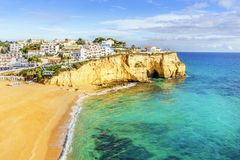 Sandy beach between cliffs in front of white architecture of Car. Sandy beach between cliffs in front of charming white architecture of Carvoeiro and turquoise Royalty Free Stock Image