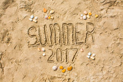 Sandy beach closeup, Seacoast sand background. Text Summer 2017. Royalty Free Stock Images