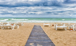 Sandy beach on cloudy day with wooden pathway and empty sun beds Royalty Free Stock Images