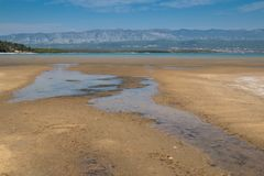 Coast of Adriatic sea, island Krk, Croatia. Sandy beach at the coast of the Adriatic sea. Puddles from the high tide and some dry grass. Mountain on the other stock image