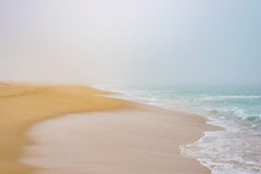 Sandy beach coast in fog, sea wave foam ocean romantic Royalty Free Stock Images
