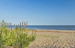 Sandy Beach com cerca e vista para o mar de piquete imagem de stock royalty free