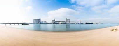 Sandy Beach com indústria no outro banco do rio Grama Fotos de Stock Royalty Free