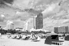 Sandy Beach com os povos que relaxam em cadeiras sob guarda-chuvas verdes foto de stock royalty free