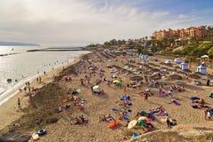 Sandy Beach com parasóis e sunbeds cobridos com sapê fotografia de stock royalty free