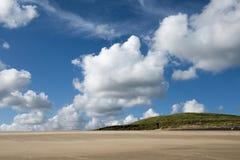 Sandy Beach com um céu nebuloso azul Imagens de Stock Royalty Free
