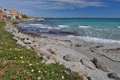 Sandy beach in the Corsican town l`Iles-Rousse. There are transparent shoal water with waves and the sandy beach in the Corsican seashore near the town L`Ile Stock Photos