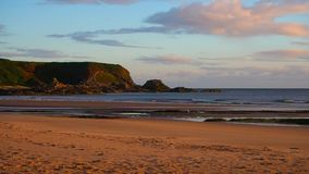 Sandy beach at dawn. August 2017: water breaks flat on the beach. The sun is rising to the east. August 2017 in Cullen Bay stock video footage