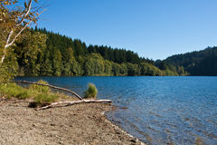 Sandy Beach on a Deep Blue Lake Royalty Free Stock Image