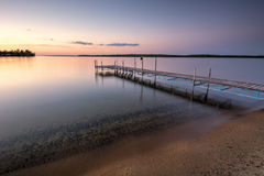 Sandy beach and dock beside lake at sunset. Minnesota, USA Royalty Free Stock Image