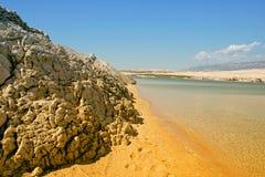 Sandy Beach en Rotsen met Blauwe Bergen Stock Foto's