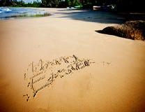 Sandy Beach feliz da Páscoa do sinal pelo oceano Fotografia de Stock