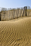 Sandy beach and fence Stock Images
