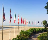 Sandy beach and flags of the different countries on the seashore. Thailand.  Royalty Free Stock Photo