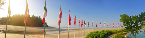 Sandy beach and flags of the different countries on the seashore. Thailand.  Stock Images