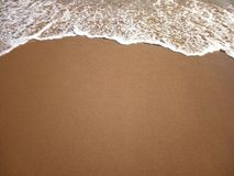 Sandy beach and a sea wave above, background royalty free stock photo