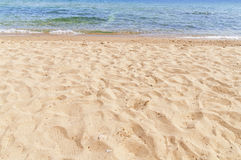 Sandy beach in foreground with sea in background Royalty Free Stock Photography