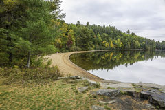Sandy Beach on a Forested Lake in Autumn - Ontario, Canada Stock Photos