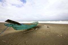 Sandy Beach with Green Boat. Green wooden boat on sandy beach with cloudy blue sky and Ocean Stock Image
