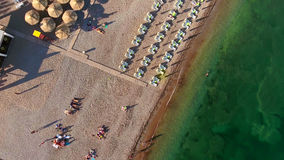 Sandy beach and green deep of sea border line, people sunbating. Top view. Europe Royalty Free Stock Photography