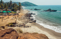 Sandy beach with green hills, palm trees, tourist relaxing in waves of Indian ocean, Goa state, India.  Royalty Free Stock Image