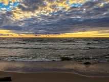 Sandy beach with grey sea waves on stormy Gulf of Finland, sunset sky Royalty Free Stock Image